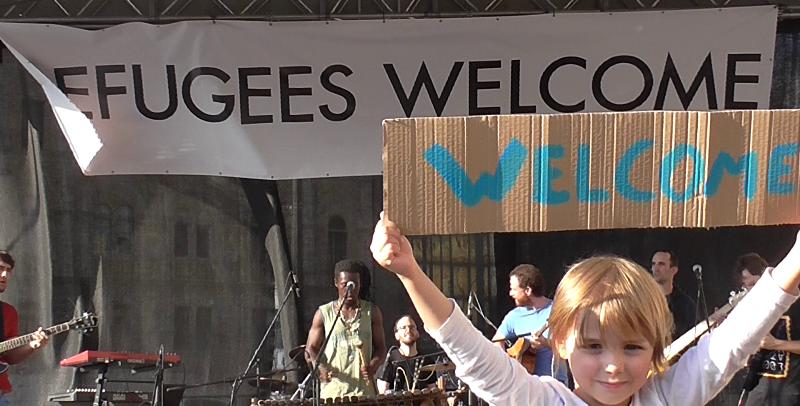 Carteles de bienvenida a refugiados en un concierto