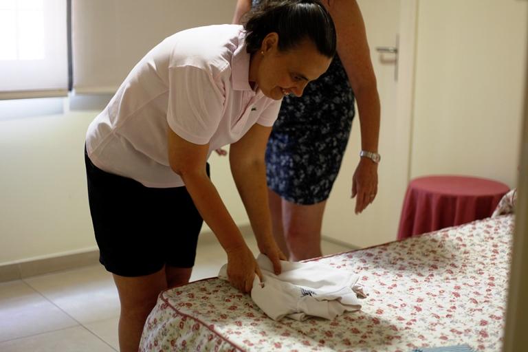 Dos mujeres doblando ropa de bebé sobre una cama