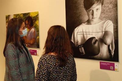 Mercedes Pérez de Prada, técnica del área de género del CERMI, explica a la Reina la exposición de fotos